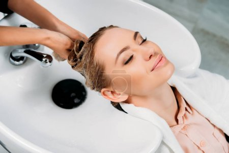 cropped image of hairdresser washing hair for customer with shampoo