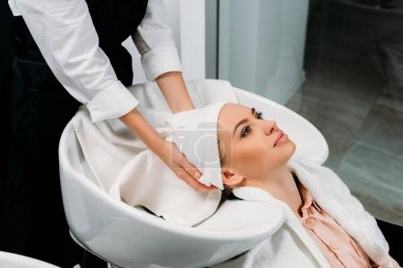 cropped image of hairdresser drying washed customer hair with towel