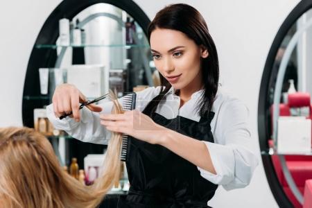 Photo pour Image recadrée de coiffeur attrayant coupe extrémités de cheveux - image libre de droit