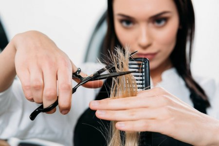 Photo pour Image recadrée de coiffeur coupe extrémités de cheveux - image libre de droit