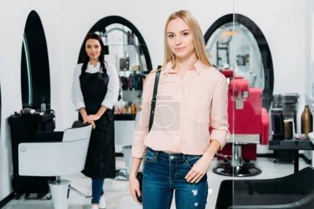 attraktive Friseurkundin steht und blickt in die Kamera