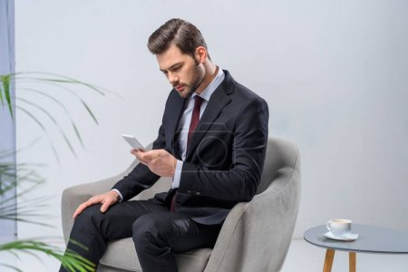 businessman sitting in armchair and looking at smartphone