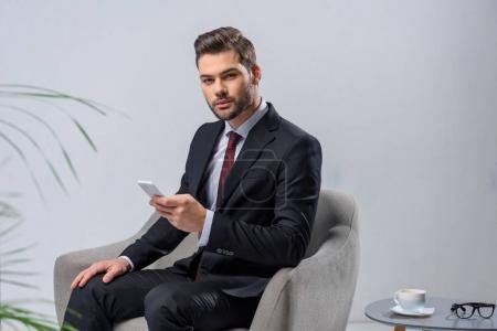 businessman sitting in armchair and holding smartphone