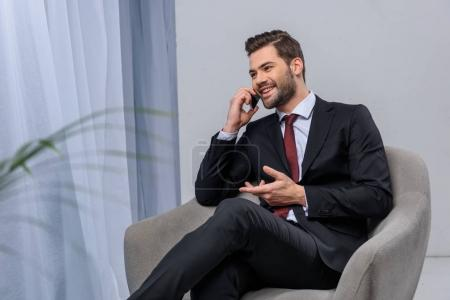 smiling businessman sitting in armchair and talking by smartphone