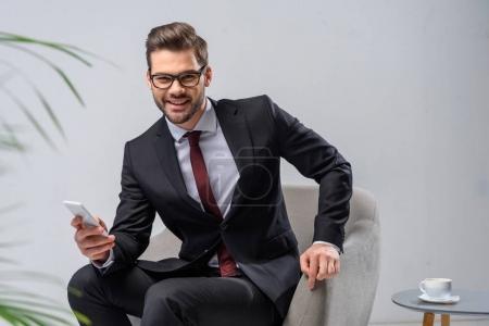 Photo pour Homme d'affaires souriant tenant smartphone et regardant la caméra - image libre de droit