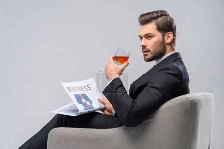 businessman sitting in armchair with newspaper and drinking whiskey