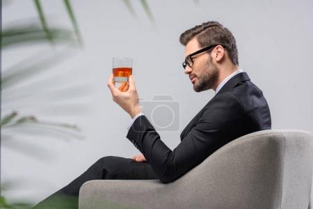 businessman sitting in armchair and looking at glass of whiskey