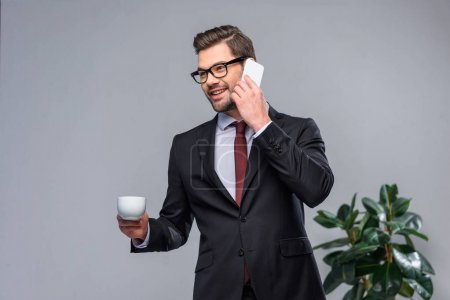 smiling businessman talking by smartphone and holding cup of coffee