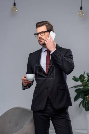 businessman talking by smartphone and holding cup of coffee