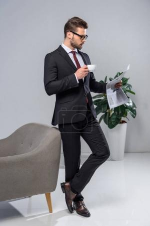 handsome businessman holding cup of coffee and reading newspaper
