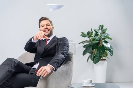 smiling businessman sitting in armchair and throwing paper plane in office