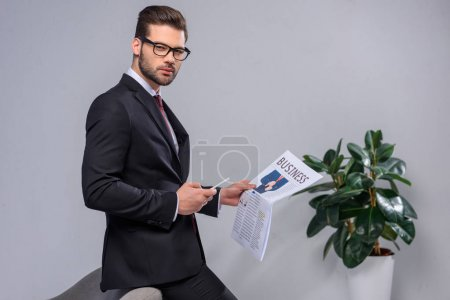 serious businessman holding smartphone and newspaper and looking at camera