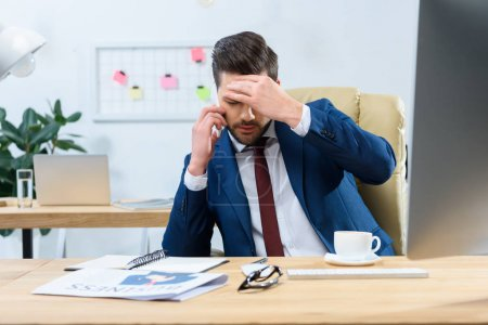 tired businessman talking by smartphone and having headache