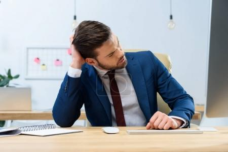 thoughtful businessman touching head and looking away