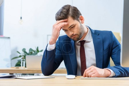 confused businessman sitting at working table and looking down