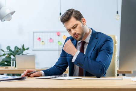 Photo for Focused businessman looking at notes in notebook - Royalty Free Image
