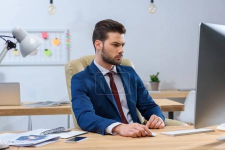 Photo pour Homme d'affaires sérieux regardant l'ordinateur sur le lieu de travail - image libre de droit