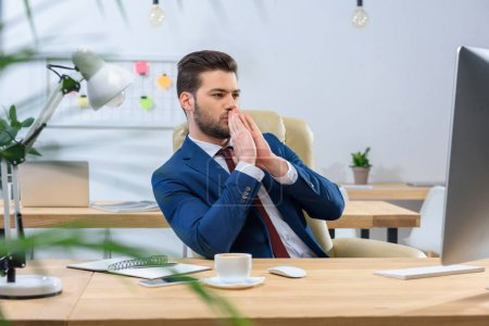 Photo for Businessman looking at computer and showing hope gesture - Royalty Free Image