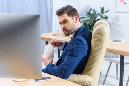businessman holding paper box with noodles and looking at computer