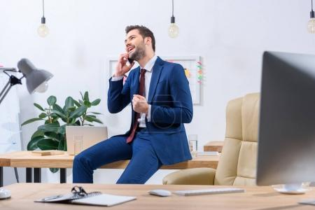 happy businessman talking by smartphone in office and showing yes gesture