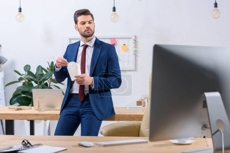 serious businessman holding paper box with noodles and looking at computer