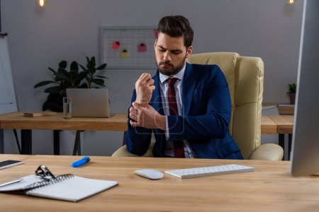 Photo for Young businessman sitting in chair and having pain in arm - Royalty Free Image