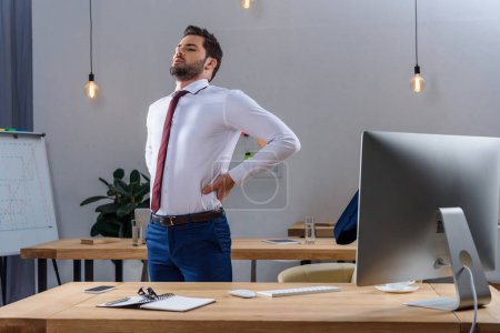 tired businessman standing and stretching in office