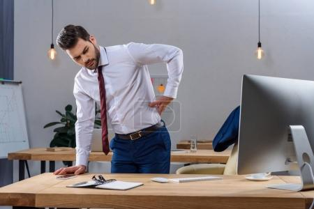 young businessman having pain in back