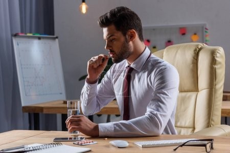 side view of sick businessman taking pill in office