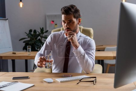 Photo for Sick businessman taking pill in office - Royalty Free Image