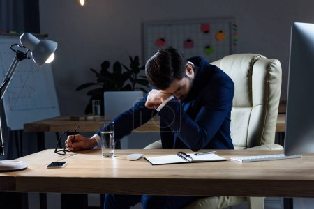 sick businessman having headache while working in evening at office