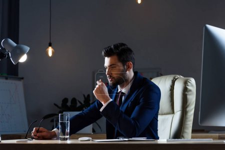 Photo for Pensive businessman sitting at working table in evening - Royalty Free Image