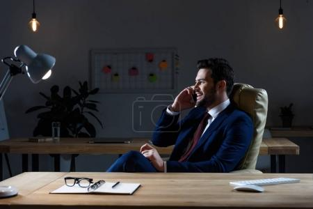 smiling businessman talking by smartphone and looking away