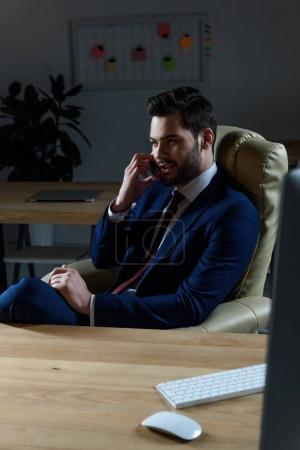 Photo pour Homme d'affaires, parler de smartphone au bureau sombre - image libre de droit