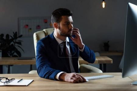 Photo for Businessman talking by smartphone and using computer - Royalty Free Image