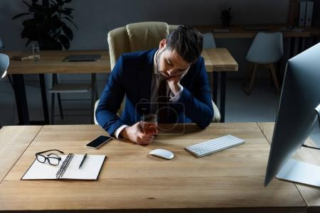 Photo for Tired drunk businessman sitting with glass of whiskey in office - Royalty Free Image