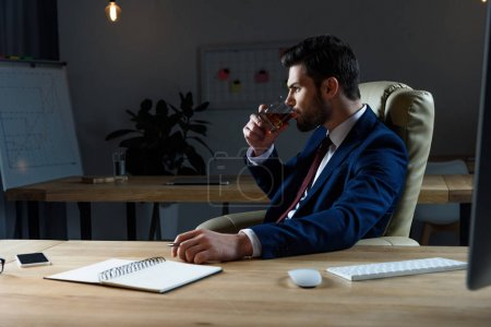 side view of businessman drinking whiskey in dark office
