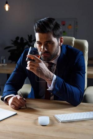 businessman drinking whiskey and looking at camera