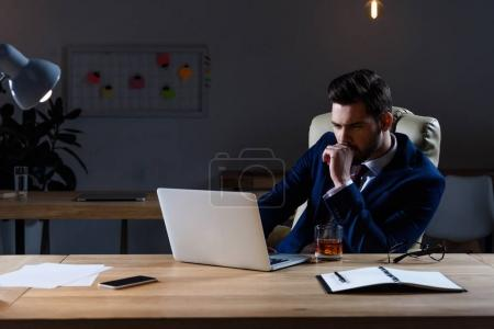 pensive businessman sitting in dark office and looking at laptop