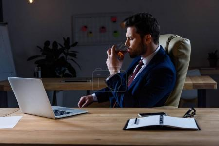 businessman sitting in dark office and drinking whiskey