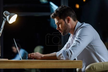 side view of businessman working at laptop in the evening