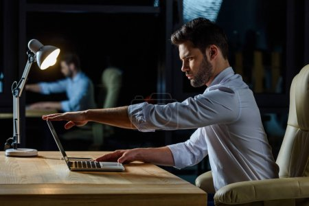 side view of businessman opening laptop at table