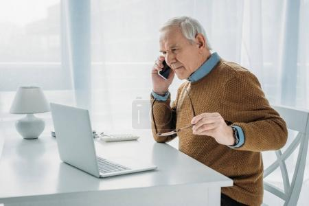 Senior busy man working by laptop and making phone call