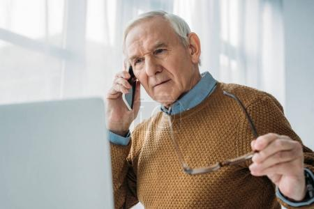 Senior busy man working in office and making phone call