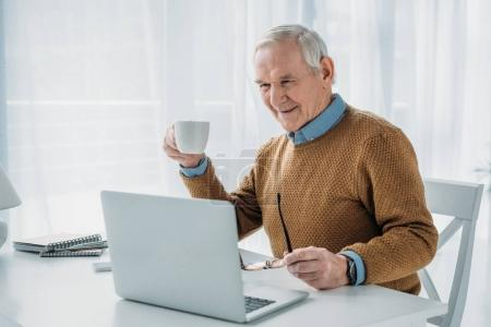 Photo for Senior confident man working on laptop and holding coffee cup - Royalty Free Image