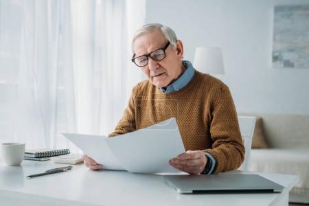 Senior-Geschäftsmann arbeitet mit Berichtspapieren