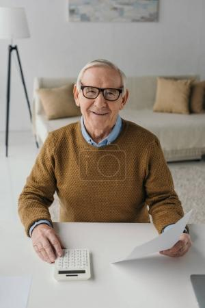 Senior confident man using calculator and holding blank paper