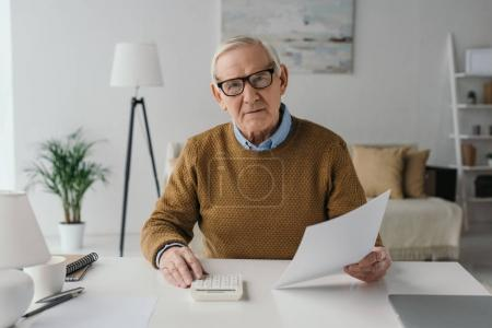 Senior smiling man using calculator and holding blank paper