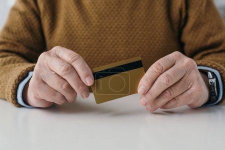 Close-up view of senior man holding credit card