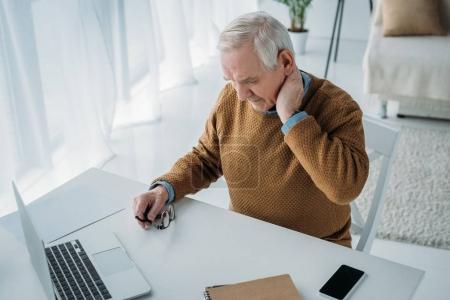 Foto de Senior hombre trabajando en oficina y sufriendo de dolor en cuello - Imagen libre de derechos
